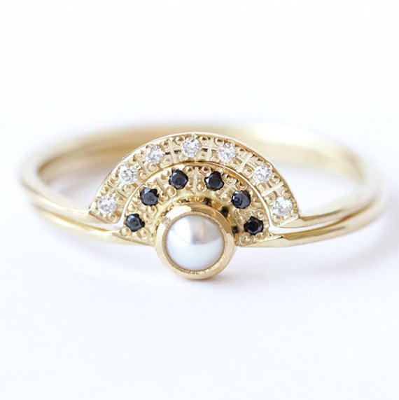 For bohemian brides, this unique set ($1,160) features a pearl engagement ring with black diamonds and a pavé diamond wedding ring.