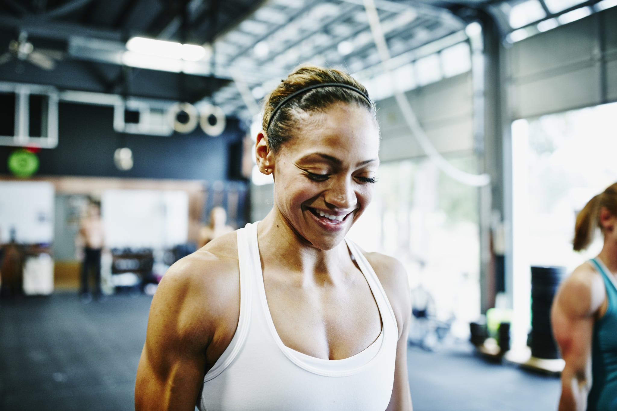 Smiling woman carrying kettlebells during workout in gym