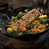 This oven-roasted Burra Fish, a Dijon-crusted sustainable fish with mixed greens, roasted vegetables, quinoa, and pumpkin seeds topped with a creamy green curry ranch dressing, can be found at Docking Bay 7 Food and Cargo.
