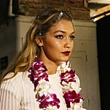 Gigi slipped into character by keeping on her lei during hair and makeup at Anna Sui.