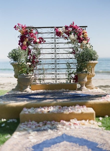 With large potted plants and gorgeous, sprawling flowers, a sculptural piece is transformed into a beautiful backdrop that's perfect for a romantic beach wedding. Photo by Braedon Photography via Style Me Pretty