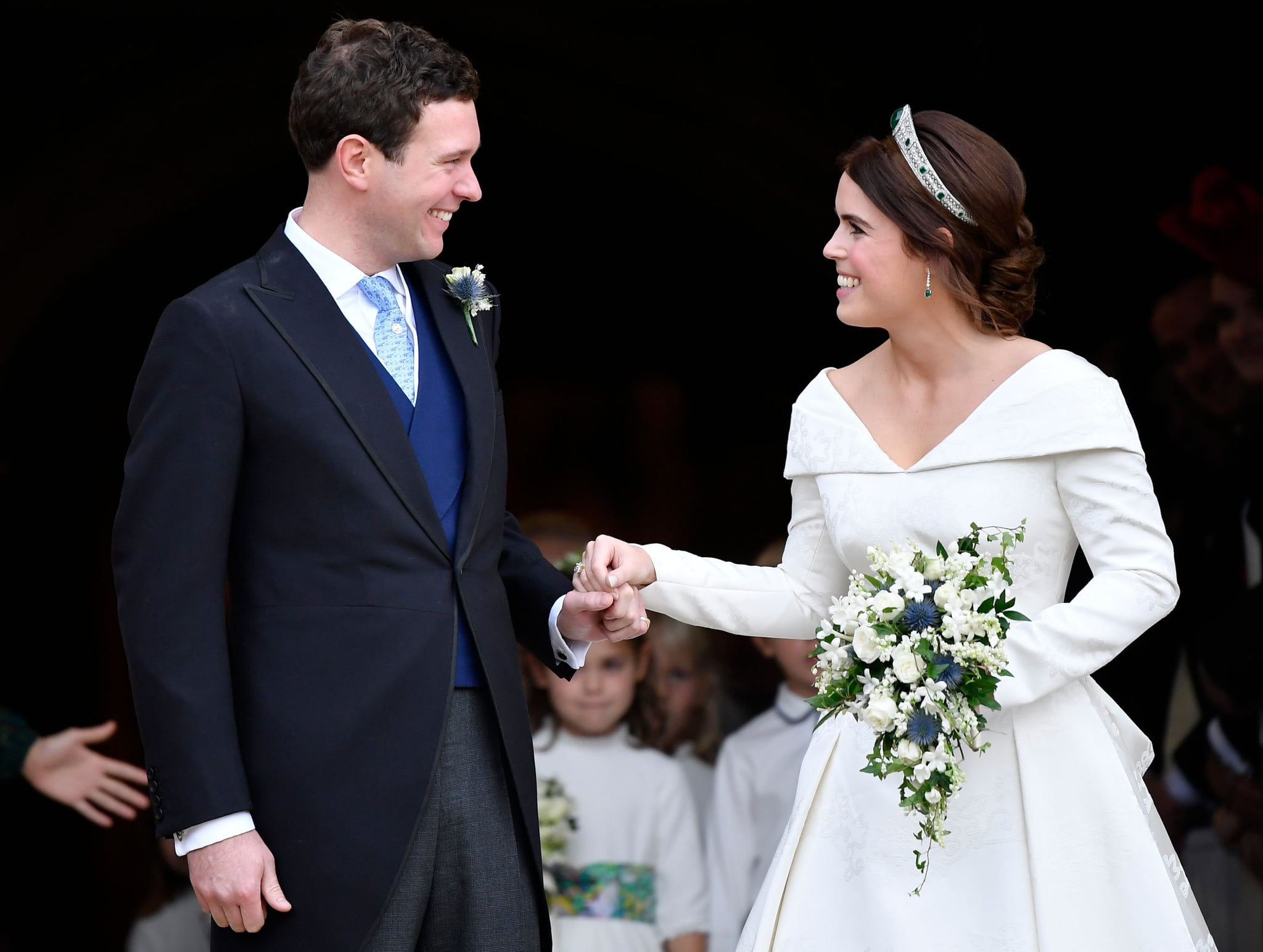 Britain's Princess Eugenie of York (R) and her husband Jack Brooksbank emerge from the West Door of St George's Chapel, Windsor Castle, in Windsor, on October 12, 2018 after their wedding ceremony. (Photo by TOBY MELVILLE / POOL / AFP)        (Photo credit should read TOBY MELVILLE/AFP/Getty Images)