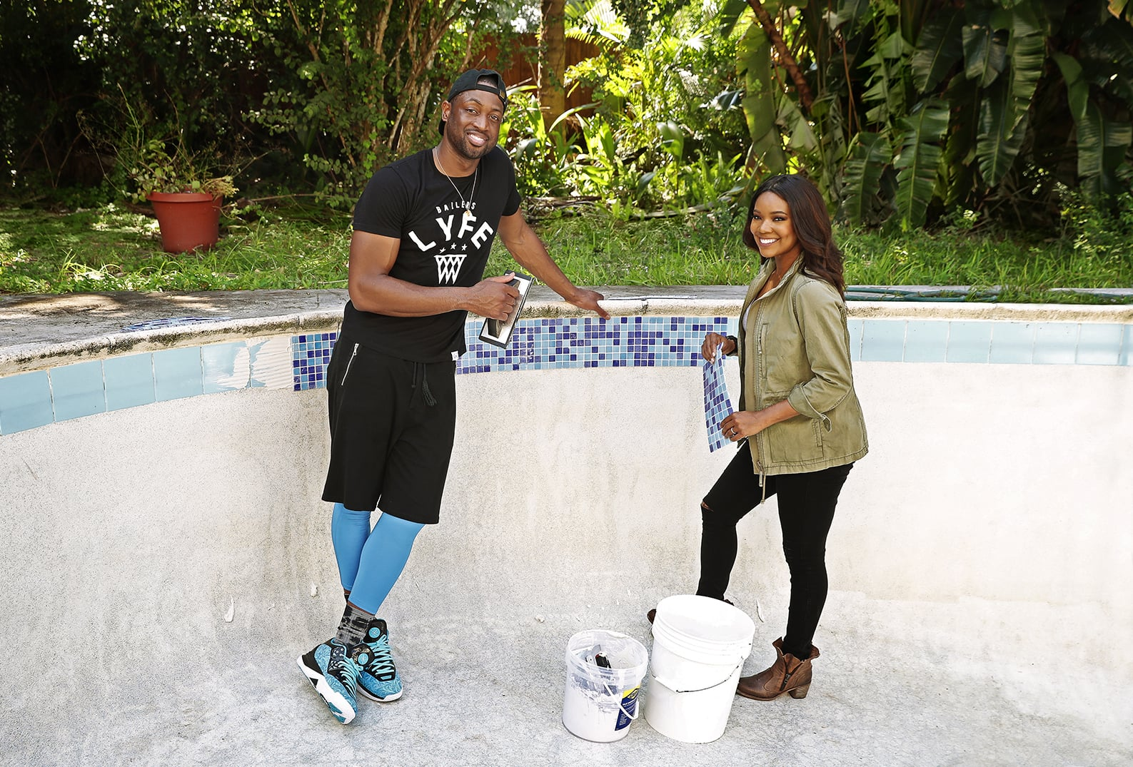 Gabrielle Union and Dwyane Wade inside the pool holding tools and tile at the home they are renovating for the Gabrielle Union and Dwyane Wade Project.