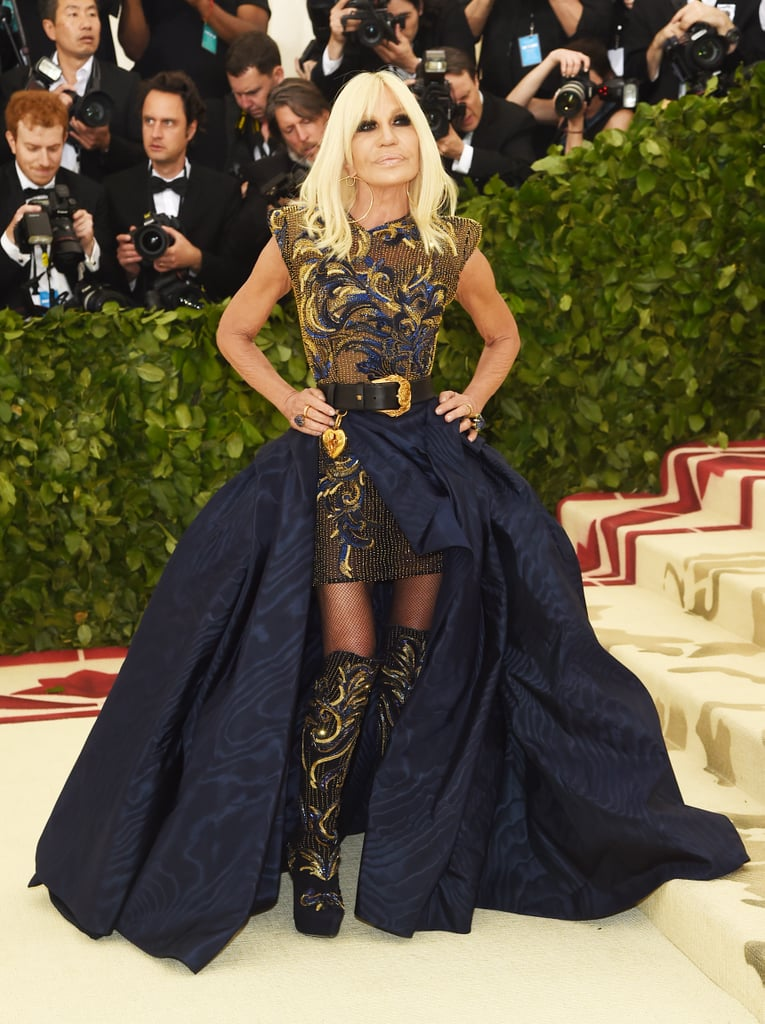 Donatella Versace has arrived! The Met Gala co-chair stepped on the creme carpet in a gorgeous Versace ensemble that looked flawless on her. Donatella's look consisted of a gold and navy embroidered minidress with a very dramatic navy blue train and a statement black belt around her waist. She definitely made a statement, but the one detail we can't get over are her boots. Her shoes match her dress — down to same gold bead detail running down the front. The 63-year-old fashion designer kept her accessories simple with a pair of large gold hoops and a pair of statement rings. Keep scrolling to see Donatella in all her glory!