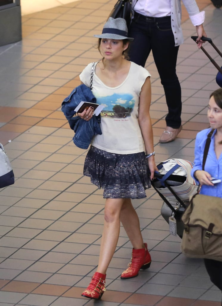 While touching down at the airport in Toronto, Marion Cotillard worked a red pair of Chloé studded boots with a printed skirt and fedora.