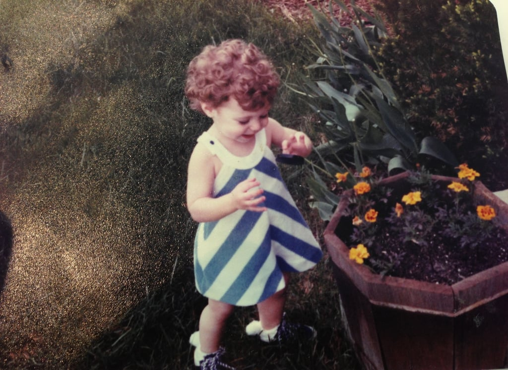 """""""I was 1 1/2. Loved the outdoors, and clearly stopping to smell the flowers. I was already showing off my love for my favorite color, blue."""" —  Lisa Sugar, editor in chief, POPSUGAR"""