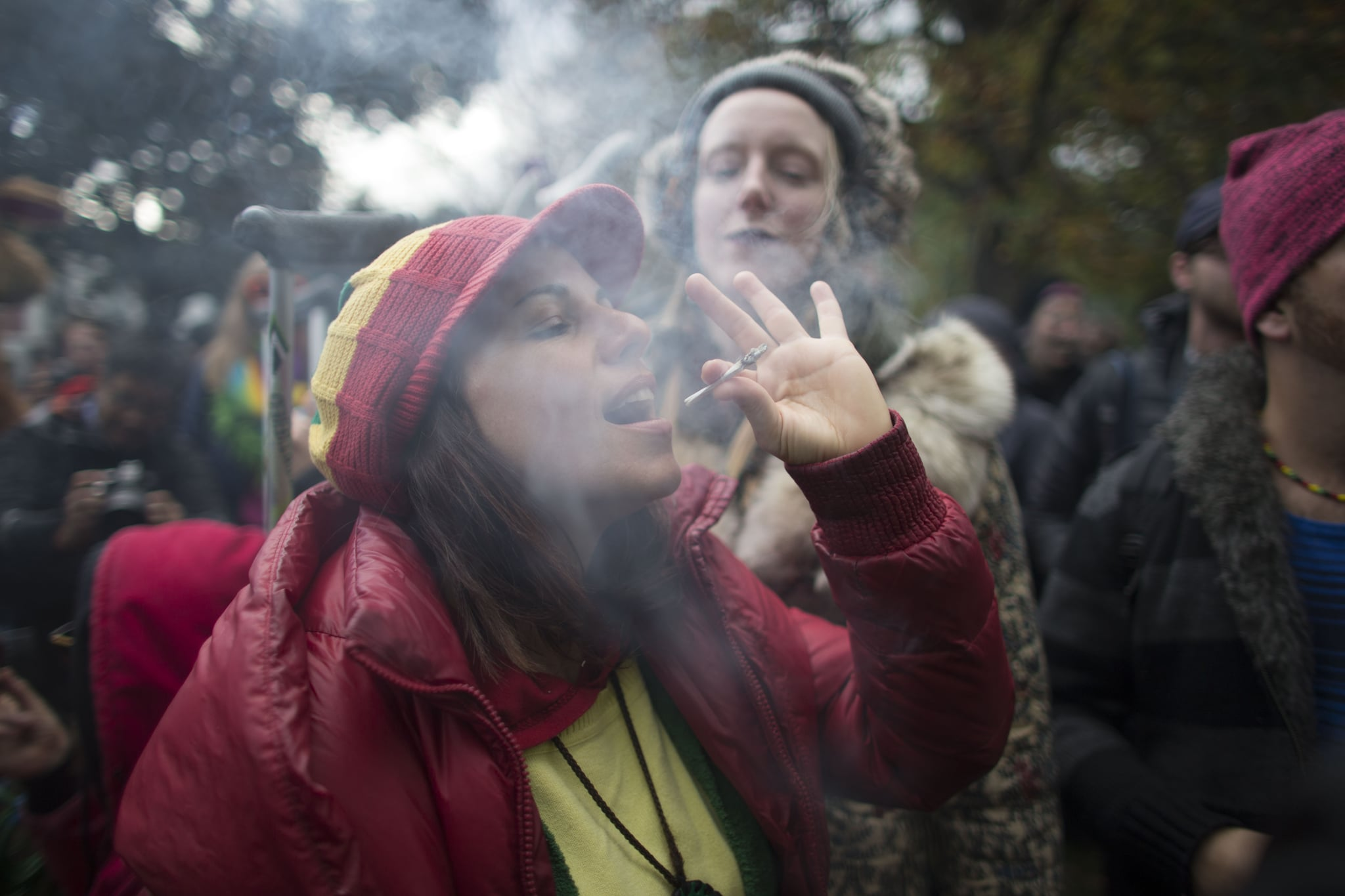 (FILES) In this file photo taken on October 17, 2018, a woman smokes a marijuana cigarette during a legalization party at Trinity Bellwoods Park in Toronto, Ontario. - Canada's health ministry warns parents against consuming cannabis because of the risks of second-hand smoke, while warning it also