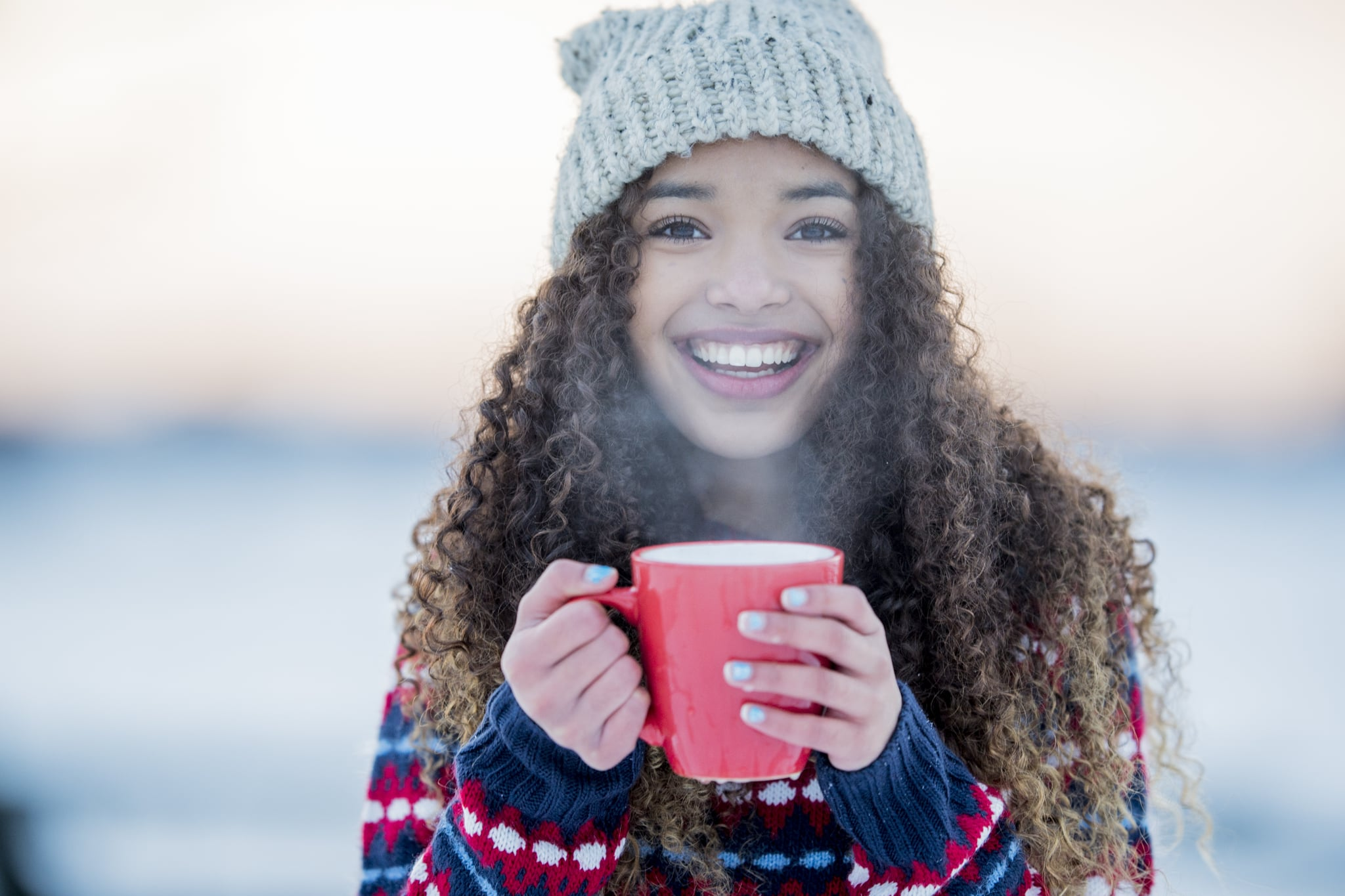 A young mixed race girl enjoys a cold winter day outside. She is smiling and holding a hot mug.