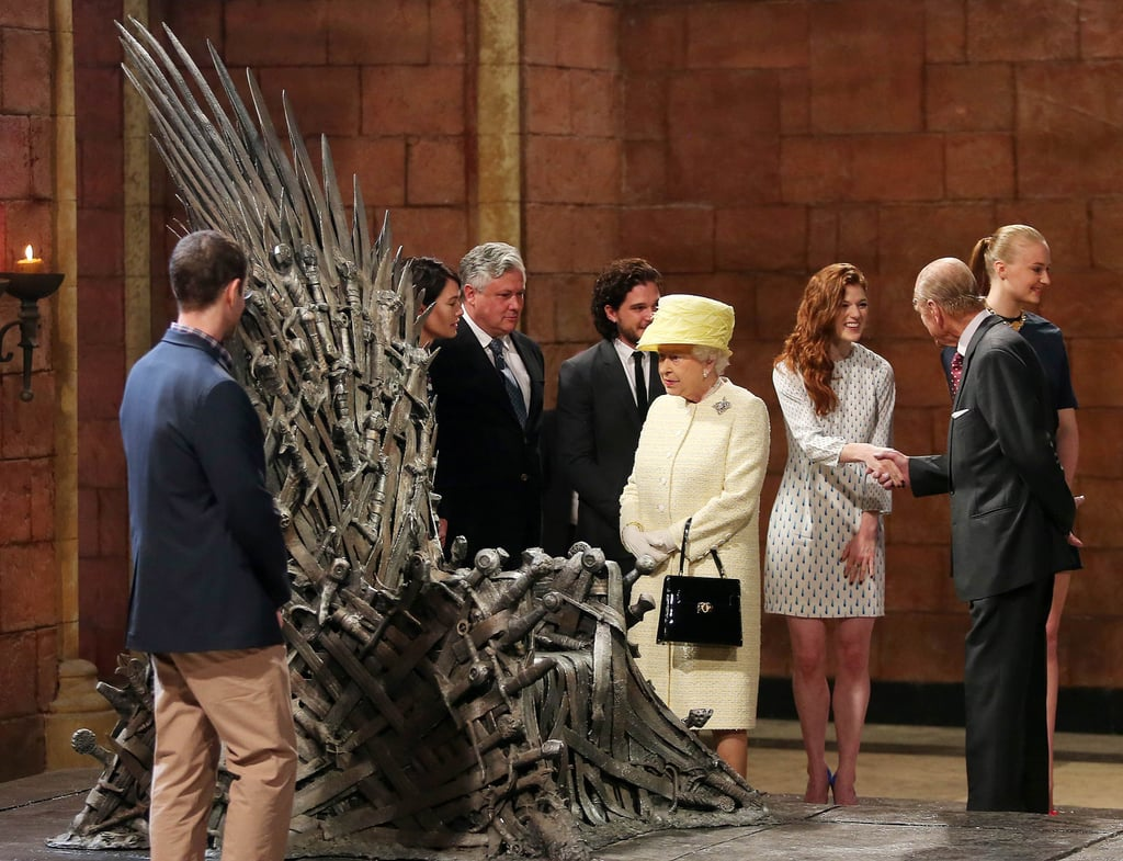 From the British throne to the Iron Throne, Queen Elizabeth II and Prince Philip, Duke of Edinburgh, made their way to the Game of Thrones set in Belfast, Northern Ireland, on Tuesday. The royals of House Windsor were greeted by both House Stark and House Lannister, as cast members Lena Headey, Kit Harington, Maisie Williams, Sophie Turner, and Conleth Hill were there for the event. During the pair's visit, they checked out props and set pieces from the show. And although the queen declined to sit on the Iron Throne of swords, she did take home a miniature statue of the throne. See all the pictures from the queen's Game of Thrones set visit below!