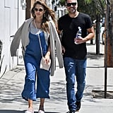 Jessica goes for a stroll with her husband on a sunny LA day. She wears a casual denim jumpsuit with a neutral tank, cardigan, and sneakers.