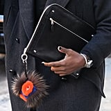 Perfect Fashion Week accessories include a Fendi charm and sleek clutch.