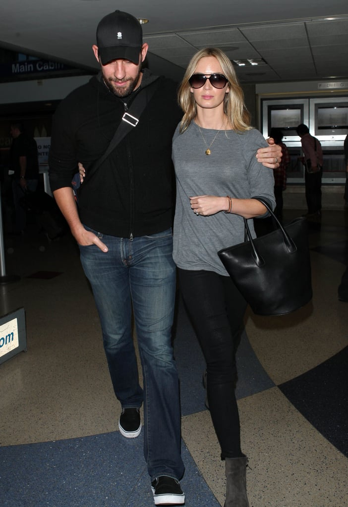 John Krasinski had his arm around Emily Blunt at the airport.