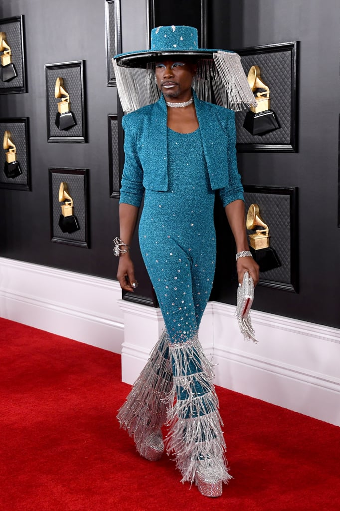 Billy Porter knows how to bring the glitz and glam to any occasion, and the Pose star truly channeled his inner Evangelista as he walked the 62nd annual Grammys red carpet on Sunday in an aqua Baja East jumpsuit with rhinestone bell-bottoms and a matching wide-brim hat that holds a very glamorous secret. The fringe-covered hat — designed by Sarah Sokol Millinery — was inspired by Billie Eilish's beekeeper-esque Burberry chain mask at the American Music Awards, according to his stylist Sam Ratelle, and features a curtain of jewels that can be opened and closed with the push of a button — now that is a look. Billy accessorized the outfit with a large bracelet shaped like a spider, a diamond collar necklace, and ring all by Alexis Bittar. His glittery fringe purse, rhinestone go-go boots, shimmering silver nails, and a thick blue cat eye bound to earn him a 10 out of 10 at any ballroom show. See Billy's incredible Grammys look from all angles ahead.      Related:                                                                                                           Sorry, Lizzo Couldn't Carry a Tiny Bag With This Badass Furry Stole