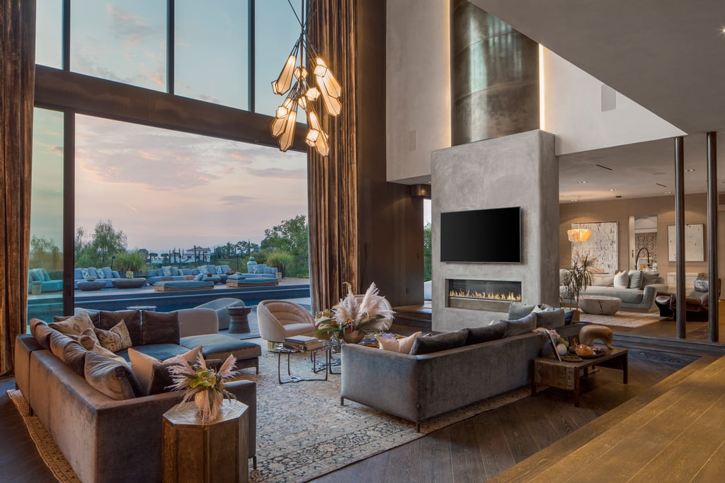 Over the years, Chrissy Teigen has given us tons of glimpses at her and John Legen's stunning Beverly Hills home. Whether it's a live stream of what she's making for dinner or dress-up tea parties with her kids, Luna and Miles, every room in their home seems to offer gorgeous views of the surrounding hills and even more gorgeous design details. But we won't get to stare are her chef's kitchen or backyard pool for much longer, because the couple just put the house up for sale for — wait for it — a casual $23.95 million!  Chrissy and John, who are currently expecting their third child together, first bought the home in 2016 (it was formerly lived in by Rihanna) and are starting the hunt for a new one as they continue to grow their family. While we already can't wait to see what house they'll buy next, we need to take a minute to appreciate this stunning piece of real estate. The house, which is over 8,200 square feet, includes seven bedrooms and eight bathrooms, a gym, a glam room, and a home theater. The entryway has 33-foot ceilings and a curving stairwell that leads to the second floor, and the large living room boasts a floor-to-ceiling glass wall with views over the canyon. Fans of Chrissy already know about the gorgeous chef's kitchen she frequently cooks in, but did you know the master suite has a brass, concrete, and clay fireplace, a balcony with stunning views, and a massive walk-in closet? Oh, and all seven bedrooms are ensuite and have their own balconies! Special decor touches include mandala-patterned ceilings from Thailand, ebonized cerused oak floors, clay-and-steel-rolled walls, onyx sinks, and Italian quartz countertops. Outside, there's a heated saltwater pool, a jacuzzi, a chef's grill, and a wood-fired oven. Chrissy and John created an open space that's also intimate, featuring not one, not two, but three separate living-room-style spaces on the first floor alone — and that's not even counting the one nestled outside by the giant pool. Ahead, see 