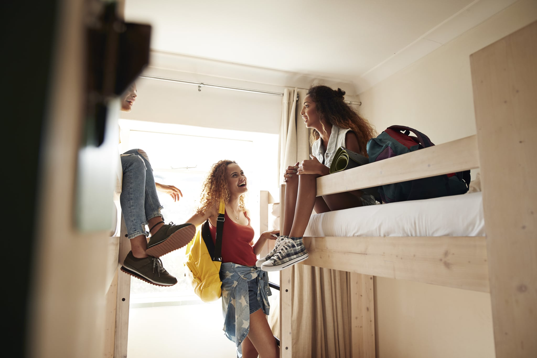 Young women having a good time and hanging out, at youth hostel with bunk beds