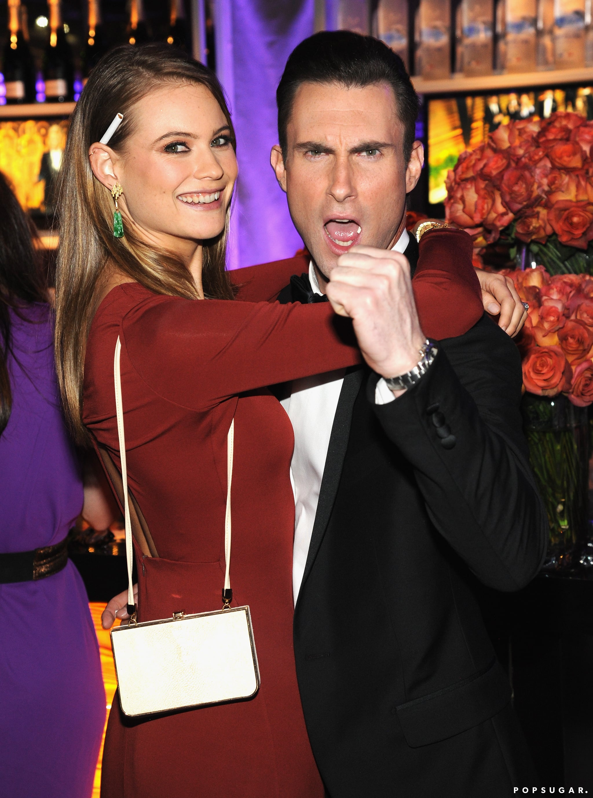 Behati Prinsloo and Adam Levine cuddled by the bar.