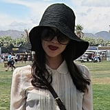 A black floppy hat protects from the sun while dark lips add drama.