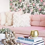 "Jessica's overarching design strategy is clearly visible in the glam living room. ""I first softened the space with textured rugs, faux fur, muted colours — blush being the new neutral — and contrasting all the grey undertones with warm brass finishes. To give the space a feminine feel, the floral wallpaper was the perfect backdrop,"" she says."