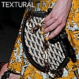 Why we love it: We love the intrigue of woven textures — some feel entirely Spring and Summer-ready, while others have that great tribal quality we love.  How to wear it: Woven totes are well suited to be your everyday bag, but a raffia clutch or smaller woven bag has that special quality that's also event-worthy.  Photo: Proenza Schouler Spring 2012