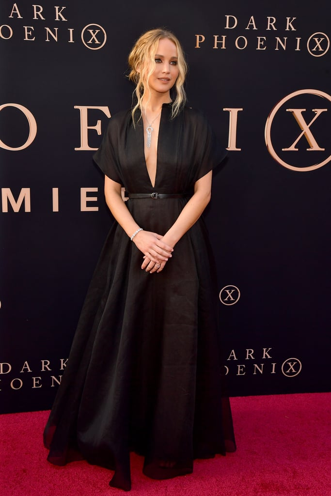 Jennifer Lawrence didn't need any bells and whistles to take our breath away with her outfit at the X-Men: Dark Phoenix premiere on June 4. Instead, she walked the red carpet in a timeless black Dior gown. Her outfit choice couldn't be more perfect for a return to the red carpet after over a year.  Jennifer's decision to wear Dior further fuels our theory that she'll wear the designer on her wedding day. After all, she's been an ambassador for the French house for years. For the premiere, she opted for a plunging silk gown from Dior Cruise 2020, cinched at the waist with a black leather belt. She paired the ensemble with a dangling silver necklace, a sparkling bracelet, and of course, her $100K engagement ring.  Keep reading to see photos of her gorgeous getup from all angles — we'd love to know what her fiancé, Cooke Maroney, thought when he saw her walk out the door.