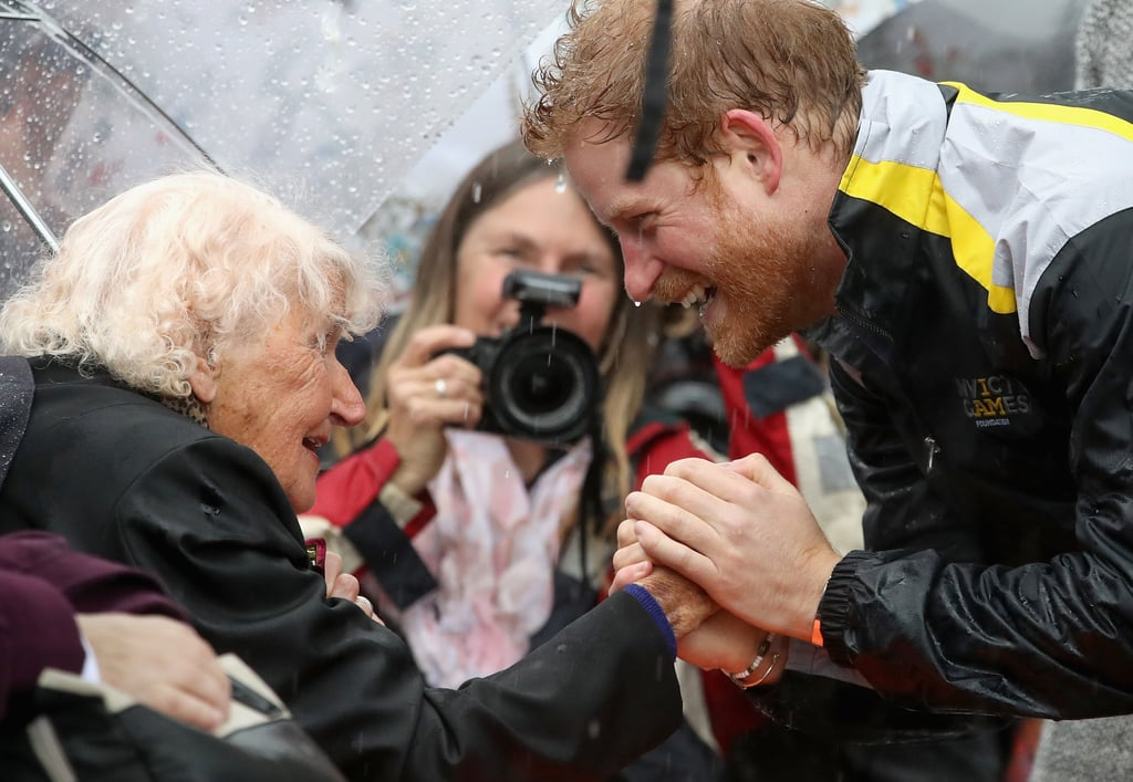 Prince Harry had a special fan waiting to greet him when he visited Sydney on Wednesday. Ahead of the 2018 Invictus Games Launch Event, the famous royal had a precious reunion with Daphne Dunne, a war widow who famously stole a kiss from him when they first met in 2015. Wearing her first husband Albert Chowne's medals, which were awarded to him posthumously after he died during the Second World War, the 97-year-old braved the cold and rain as she waited for Harry. Not only did the 32-year-old recognize her right away as he greeted her with a warm hug, but she even stole another kiss from him — this time on the other side. The prince has certainly been keeping busy these past few weeks. Aside from preparing for the Invictus Games in September, Harry recently traveled to Singapore for the first time to visit the Jamiyah Education Centre and partake in a charity polo match for his organization, Sentebale.