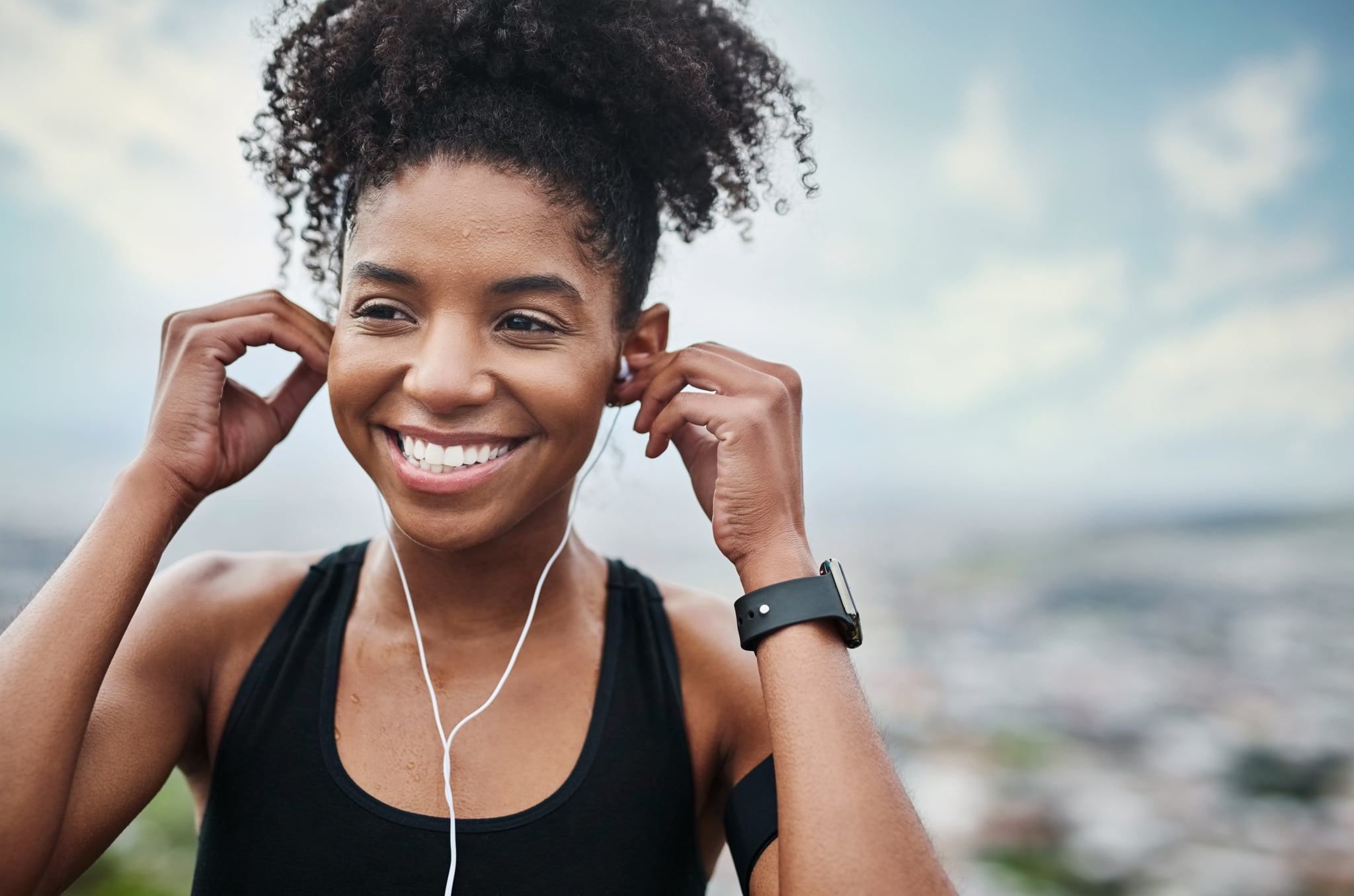 Shot of a sporty young woman listening to music while exercising outdoors
