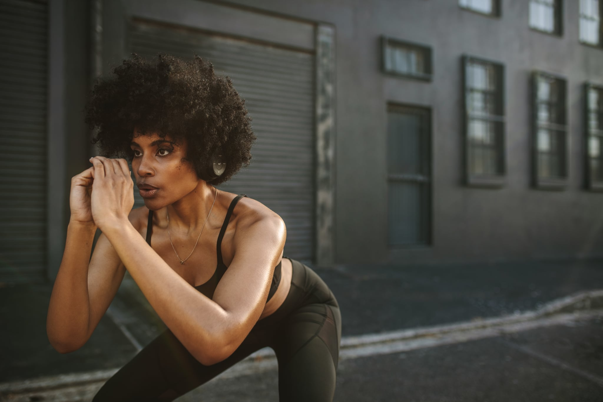 Young woman practicing squats in city. Female athlete exercising outdoors in morning.