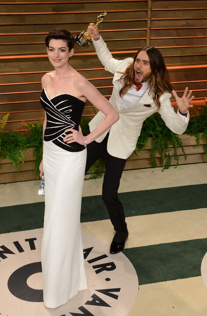 Jared Leto gave his best attempt at a surprise photobomb on Sunday night when he teased Anne Hathaway on the red carpet at Vanity Fair's annual post-Oscars bash. Jared, who was still holding his best supporting actor Oscar, attempted to creep up on Anne, who had won best supporting actress last year, but she turned around and caught him in the act. Luckily for Jared, she saw the humor in it and giggled with him on the carpet as they both posed for photos together.  Photobombing appears to be the thing to do at this year's Oscars, as many more stars got in on the fun on Sunday night. Glenn Close photobombed Ben Affleck and Jennifer Garner at the Vanity Fair fete, and Benedict Cumberbatch punked U2 by jumping on on their group snap on the red carpet at the Academy Awards. And let's not forget Ellen DeGeneres's surprise videobomb of Leonardo DiCaprio and Sandra Bullock, which shocked both actors.