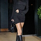 Victoria in a bishop-sleeved jersey dress and knee-high boots in London in 2006.