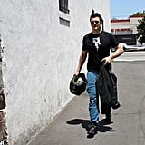 Orlando Bloom walked with his jacket in one hand and helmet in the other.