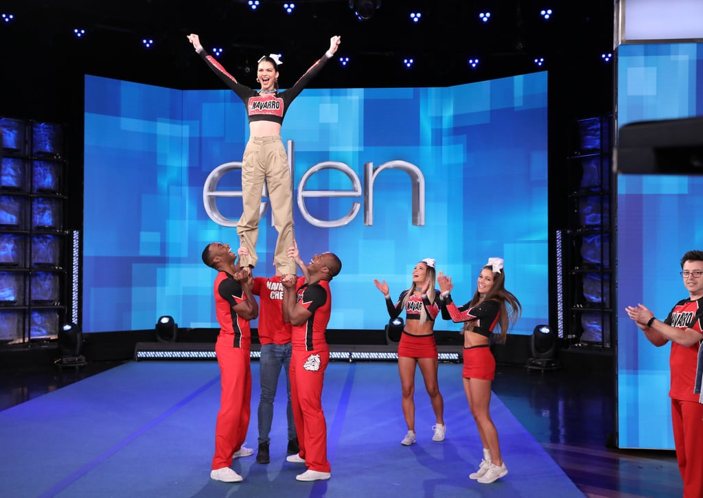 """Like most of us, Kendall Jenner is a huge fan of Netflix's Cheer. On Thursday, the 24-year-old model gushed over the heartwarming docuseries during an appearance on The Ellen DeGeneres Show, admitting that her brief stint as a cheerleader in high school wasn't nearly as rigorous as Navarro's program. But she got a chance to work with the cheer masters when Ellen brought out a few members of the Navarro squad to teach her a simple prep stunt. After a nervous start, she quickly got the hang of things, saying, """"This is amazing!"""" Watch Kendall learn the stunt ahead, then check out more photos from her visit!       Related:                                                                                                           Want to Keep Up With the Stars of Netflix's Cheer on Social Media? Here's a Handy List"""