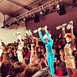 Models exercising with champagne bottles at Betsey Johnson.