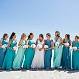 This large bridal party group wore teals, seafoam greens, and blues.