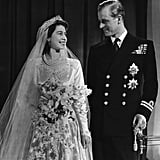 """The bride's bouquet had special meaning. Queen Elizabeth II's wedding bouquet came from the Worshipful Company of Gardeners. It was specifically arranged by florist MH Longman, who chose white orchids and a sprig of myrtle with special significance. The myrtle came from a bush that was grown from a sprig used in Queen Victoria's wedding bouquet (insane, right?!). Years later, at the Queen's Golden Wedding celebration in 1997, she was gifted an identical bouquet.   She continued the tradition of putting her bouquet on the tomb of the Unknown Warrior. The only stone not covered by the special carpet used in Westminster Abbey on the day of Elizabeth and Philip's wedding was the grave of the Unknown Warrior. The Queen also kept with the tradition started by her mother of returning to the grave the day after she tied the knot, and placing her beautiful bouquet on the stone. The tradition has continued ever since (Kate Middleton did the same thing when she married Prince William!).   It was one of the first TV weddings, so to speak. The ceremony was broadcast via radio the day of, and later a film of the day was shown in movie theaters around the country.  Their gift table basically could've stretched a mile long. Well-wishers around the world expressed their joy for the couple in the form of over 2,500 gifts. Most of them were put on display for a charity exhibition at St. James's Place in 2007, where over 200,000 visitors showed up to take a look at what Philip and Elizabeth been given.   They hosted a wedding """"breakfast"""" after the ceremony. Guests congregated at Buckingham Palace to dine on Filet de Sole Mountbatten, Perdreau en Casserole, and Bombe Glacee Princess Elizabeth. Like Elizabeth's dress, the event relied on a charity donation to make it a possibility. The  nine-foot-tall wedding cake (which was a whopping 500 lbs.!) was made from ingredients donated by the Australian Girl Guides. To repay the kindness, the couple didn't eat the cake at their reception. Inst"""