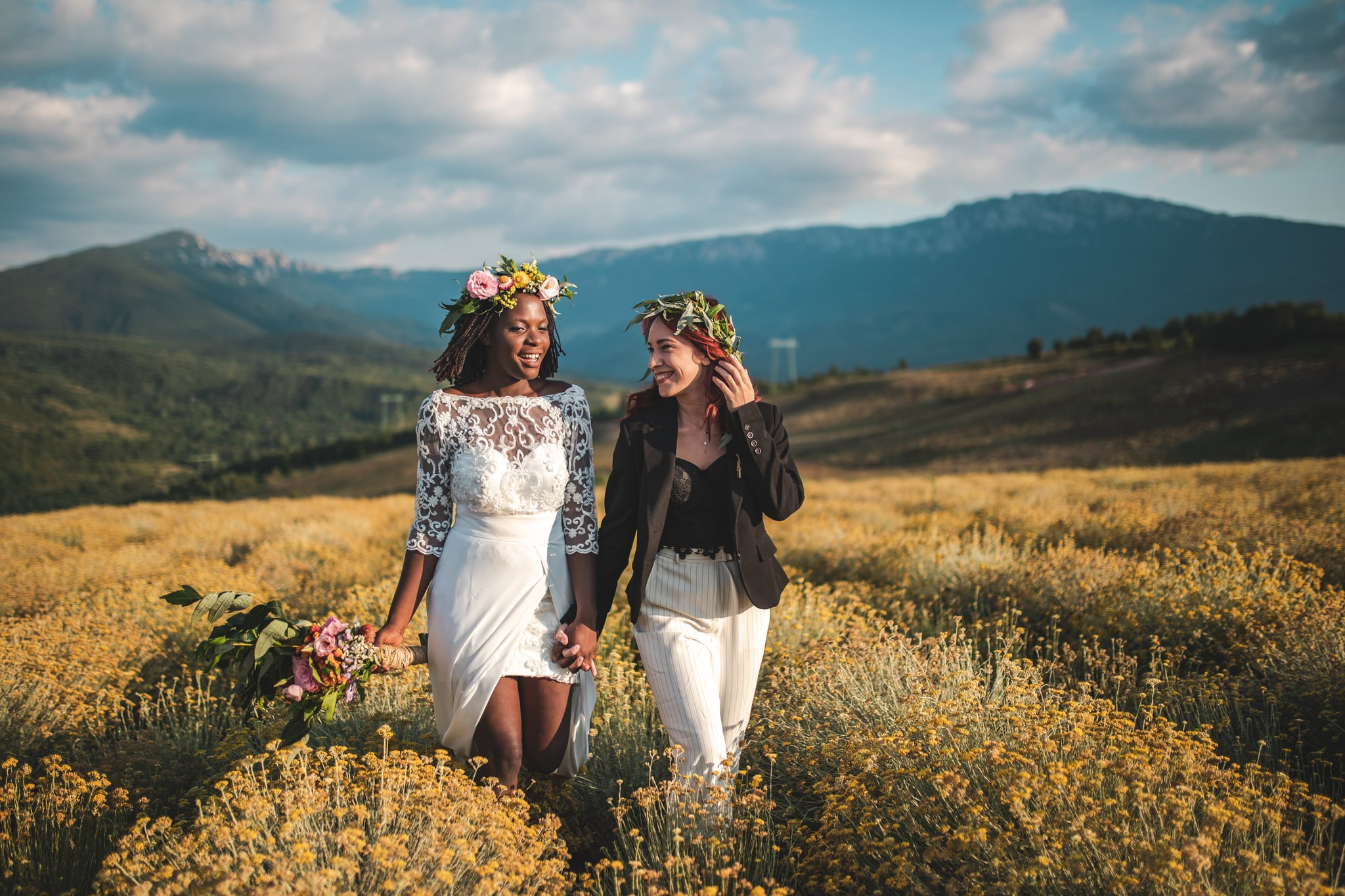 Two beautiful, young women holding hands and walking on meadow on their wedding day
