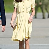 Kate's effortless plane look consisted of this bright yellow Jenny Packham number, plus a box clutch and nude pumps, both by L.K. Bennett.