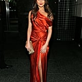 Chrissy Teigen struck a pose wearing an orange off-shoulder draped gown paired with a metallic clutch and sandals.