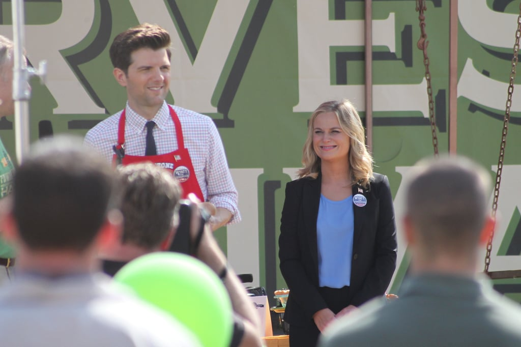 Scott and Poehler stand on stage for a scene.