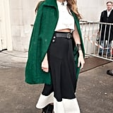 Elisa Sednaoui played with proportions, choosing a cropped top and a long skirt to go with her kelly green overcoat, at Chanel.