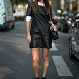 Add femininity to a black leather jumper by layering it atop a cuffed white blouse.