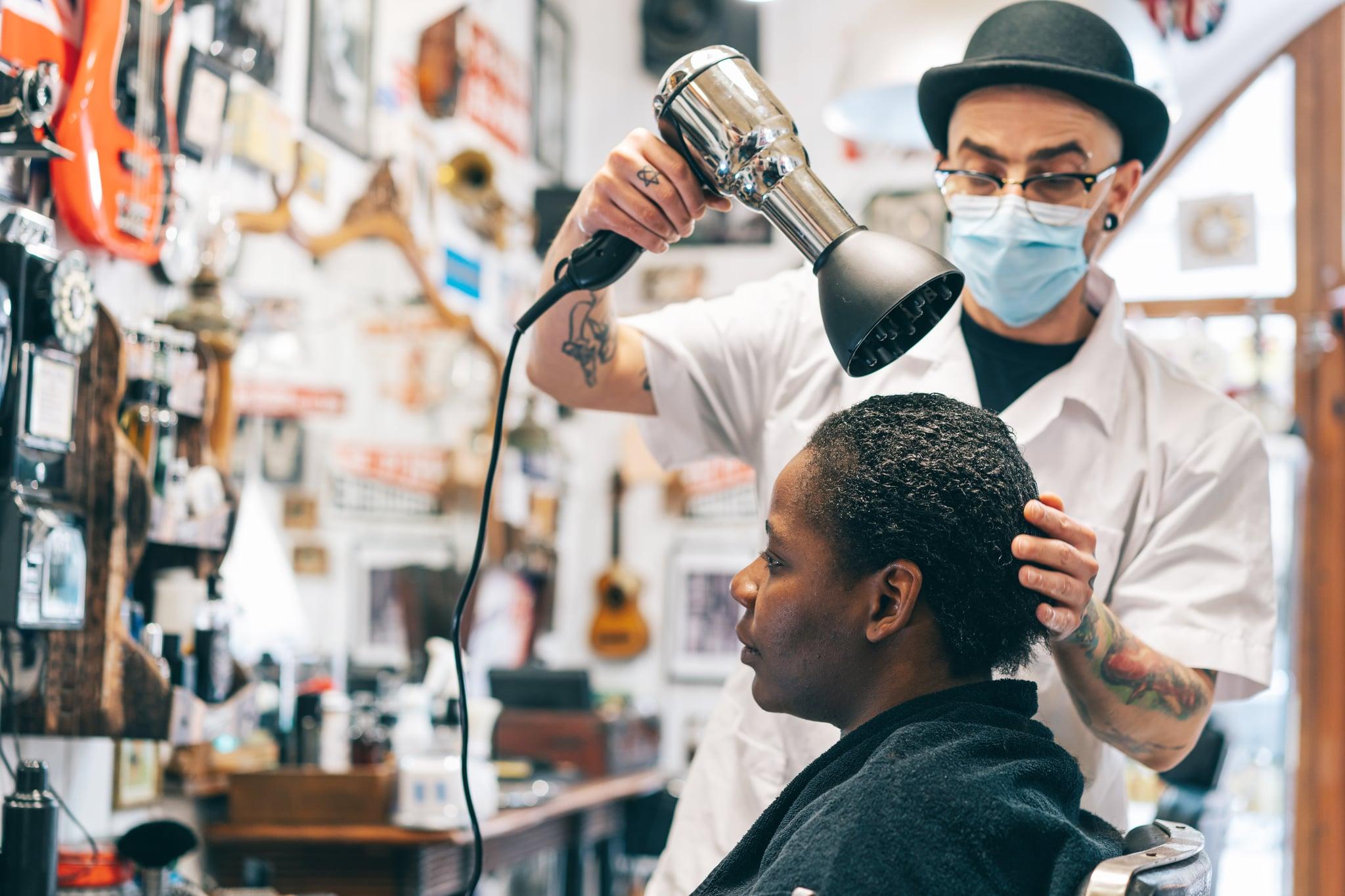 آرایشگاه مرد با ماسک محافظ صورت و خشک کردن موهای زن با سشوار در استودیوی زیبایی