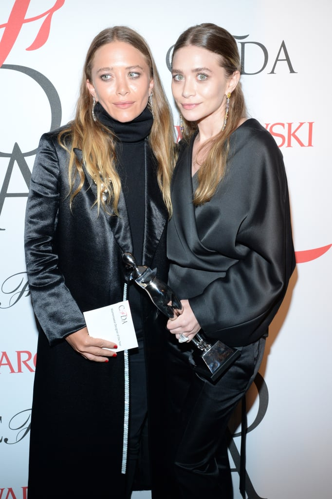 At the 2015 CFDA Fashion Awards, the twins post with their award both wearing center parts.