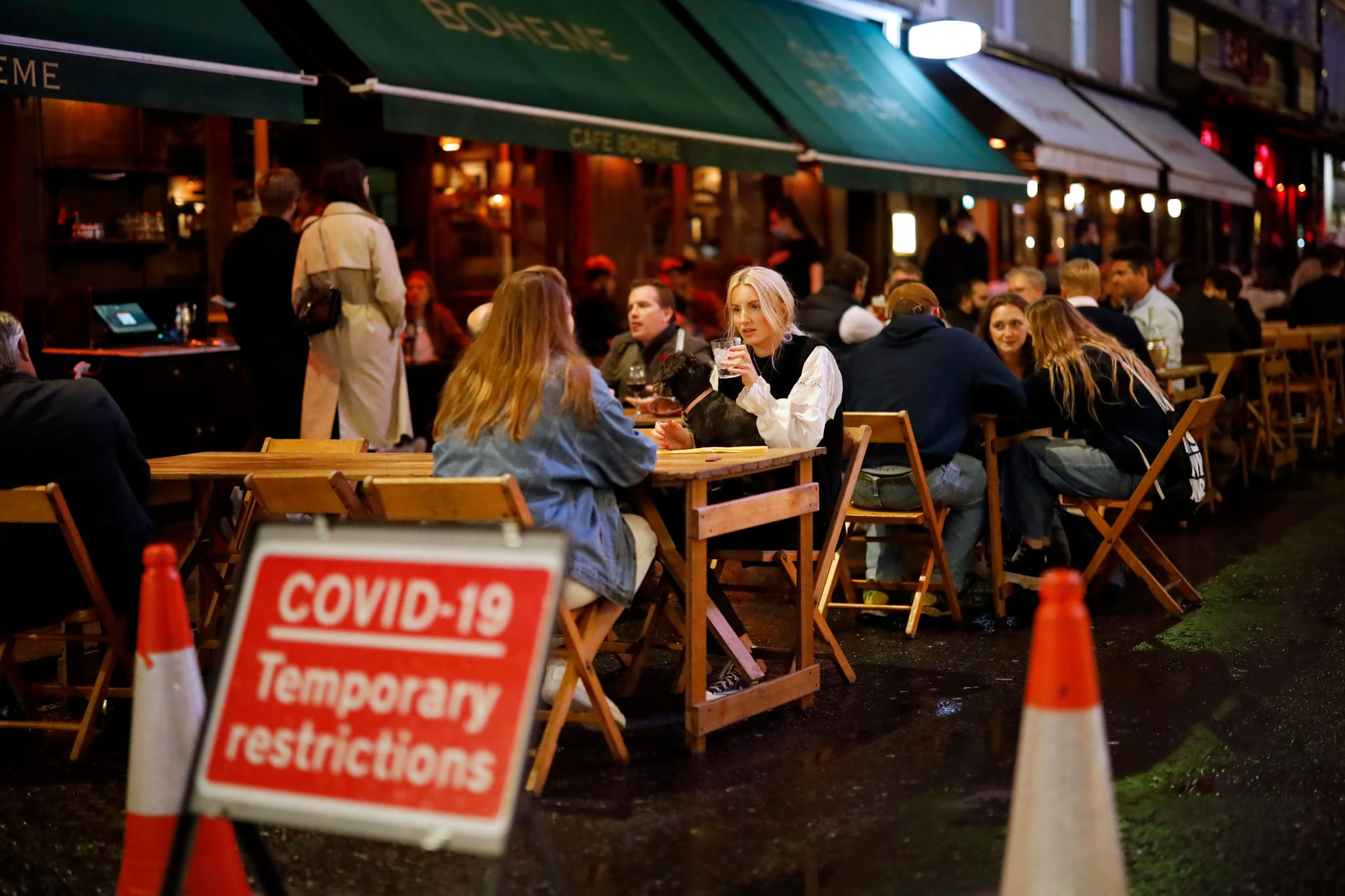 People drink at the outside tables of a cafe in Soho, in central London on September 23, 2020. - Britain on Tuesday tightened restrictions to stem a surge of coronavirus cases, ordering pubs to close early and advising people to go back to working from home to prevent a second national lockdown. (Photo by Tolga Akmen / AFP) (Photo by TOLGA AKMEN/AFP via Getty Images)