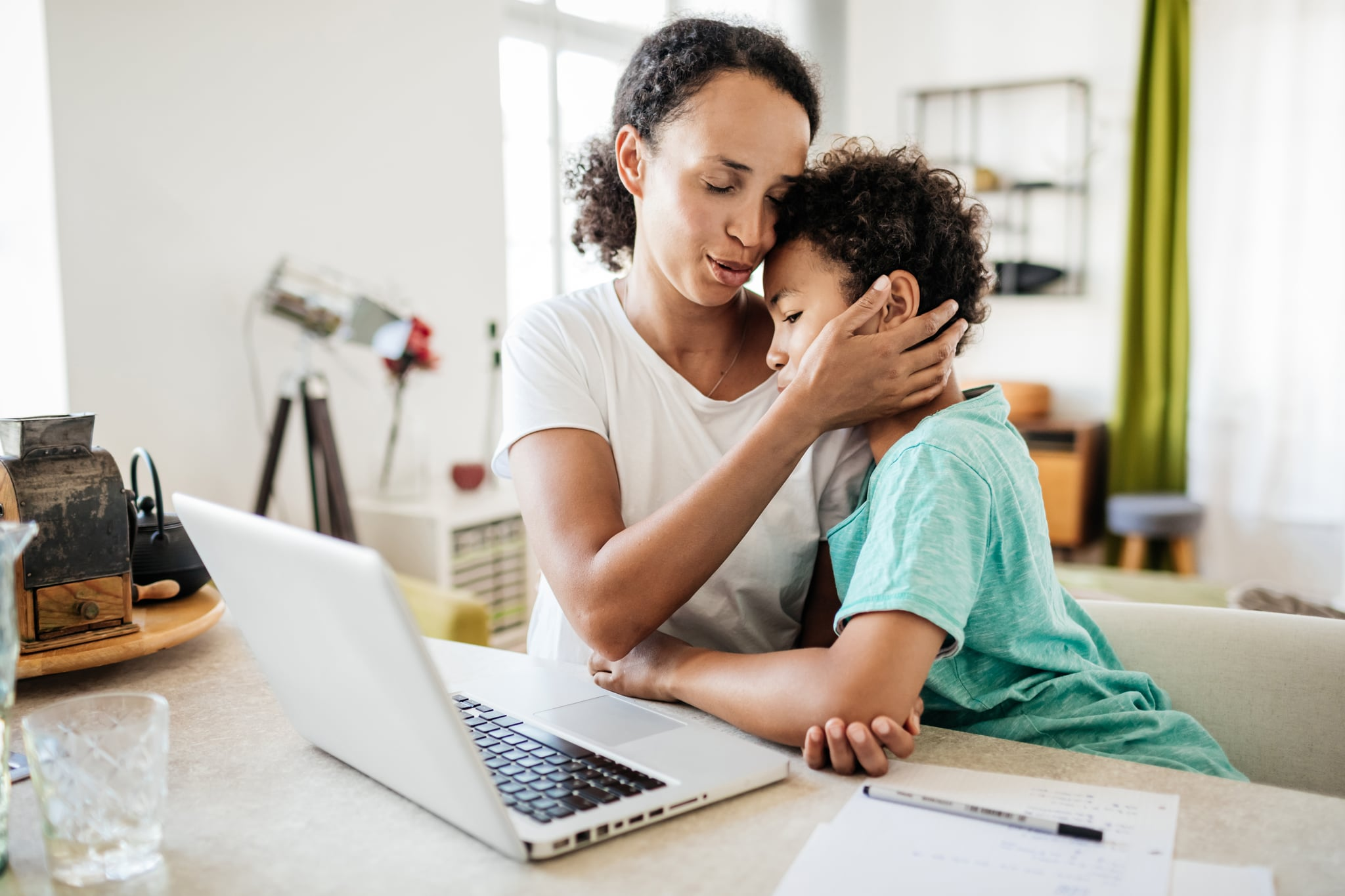 A single mom affectionately holding her young son  while she works from home in her kitchen using a laptop.