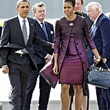 Leaving London, Michelle chose a purple ombré Peter Som dress and coat.