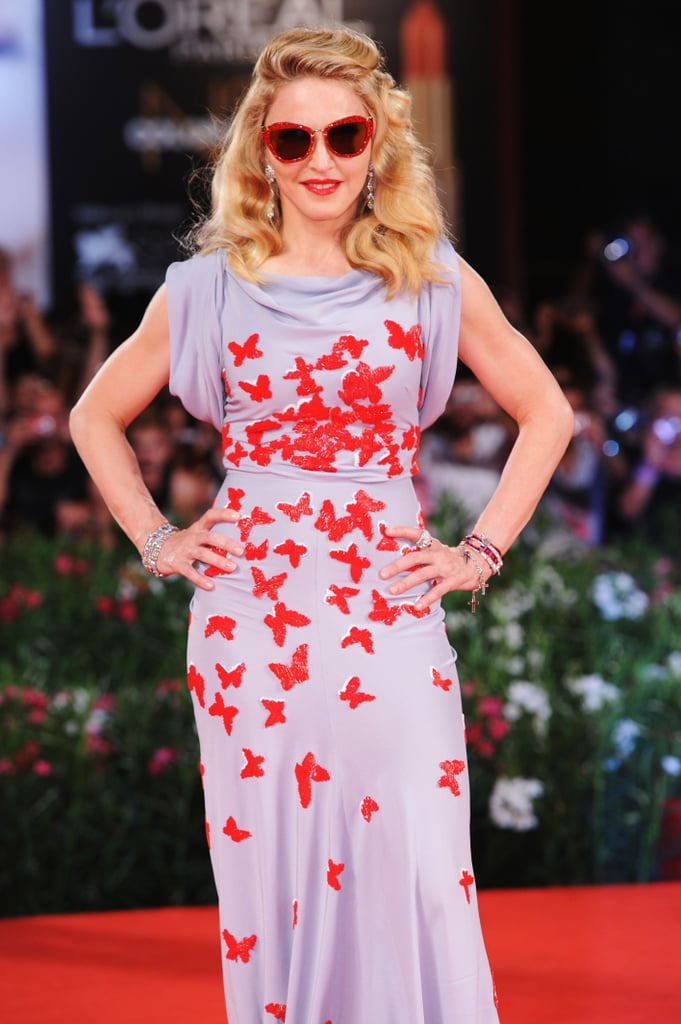 Madonna stepped out in a butterfly-bedecked Vionnet gown and matching sunglasses as she debuted her directorial project W.E. at the Venice Film Festival this evening. The multitalented Madge gave the stars of her film, Abbie Cornish and Andrea Riseborough, a warm welcome on the red carpet, and she also had fans in Valentino and Marisa Tomei, who both turned up at the event. Reviews of W.E. have been mixed, but the period piece is so far faring better with the critics than her first effort behind the camera, 2008's Filth and Wisdom. Earlier today, Madonna gave a press conference to talk about the movie and credited her exes Sean Penn and Guy Ritchie with encouraging her directorial dreams. Madonna has dated several men in Hollywood, but the creative talents of her current flame lie elsewhere; Madonna's new beau, 24-year-old Brahim Zaibat, is a professional breakdancer.