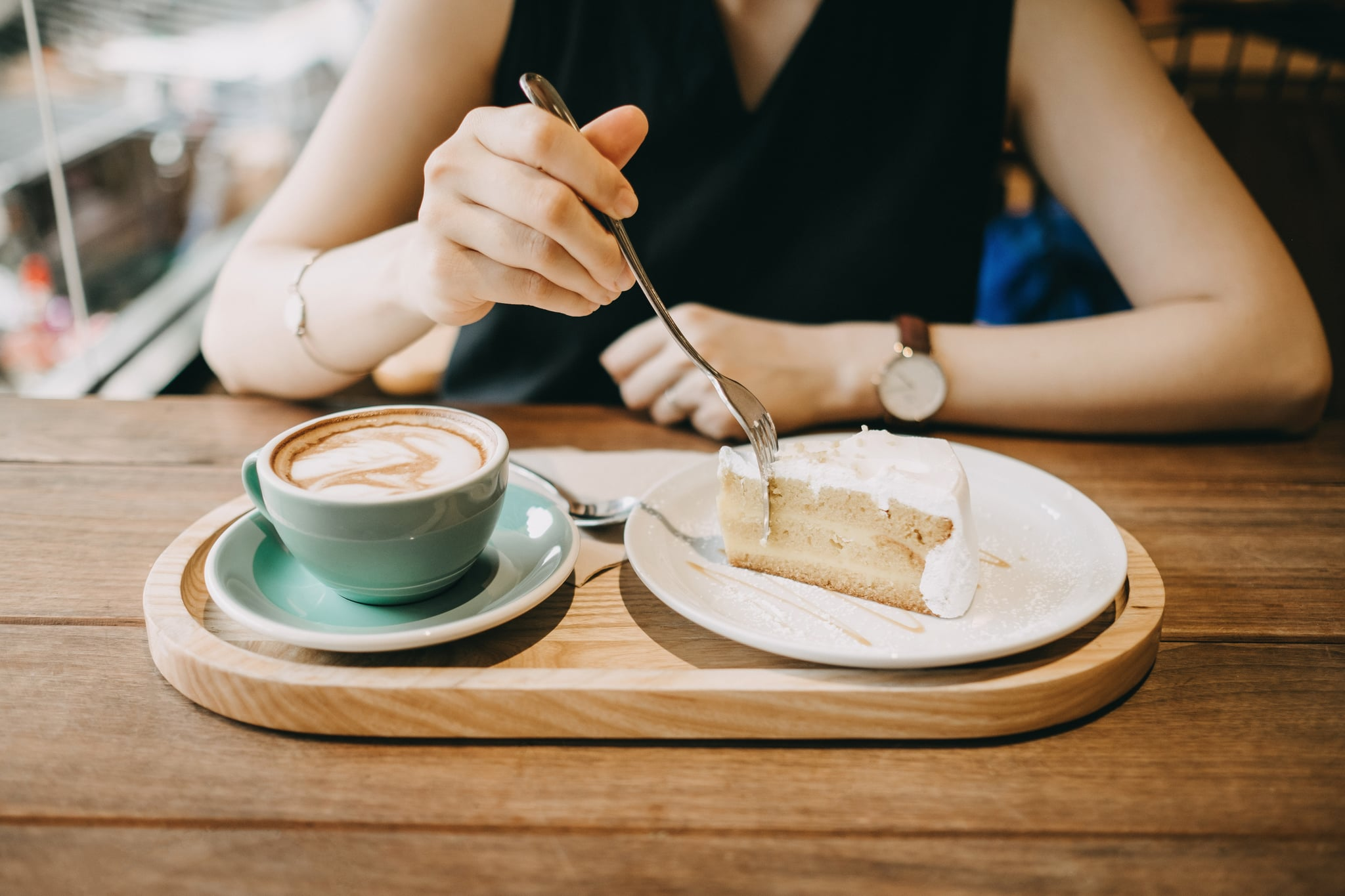 Woman having a relaxation time eating a slice of cake and having coffee in cafe