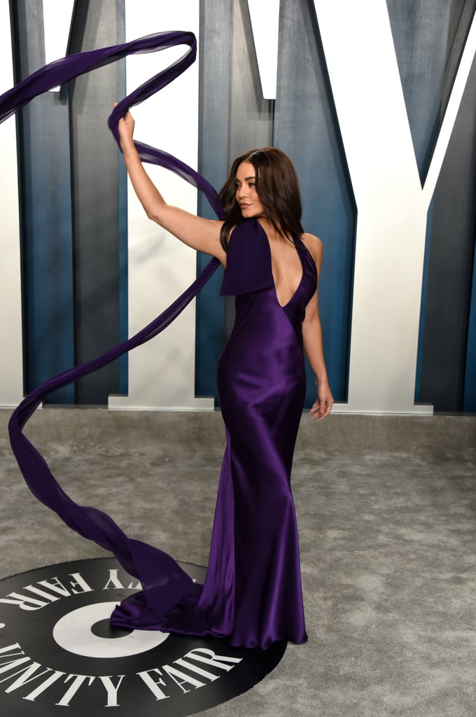 It's easy to spot Vanessa Hudgens at the Vanity Fair Oscars afterparty — she's having the time of her life showing off her Vera Wang gown. The purple silk halter dress includes a statement bow with a long train. Hudgens knows how to rock a red carpet, so she's been tossing the train in the air like a professional ribbon dancer. Hudgens chose the perfect gown to show off her new tattoo — it just barely peeks out of the gorgeous design. Take a look at all the fun photos the star took before heading into the party.
