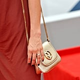 Her gold chain-strap Gucci bag put a metallic twist on her sultry red look.