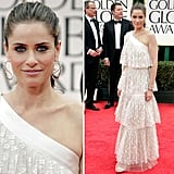 Amanda Peet made quite a statement on the 2012 Golden Globes red carpet. The actress paired an ivory frothy, tiered gown with metallic heels. We love the soft lace layers and simple, yet bold jewels via a silver bracelet and unique gold earrings.